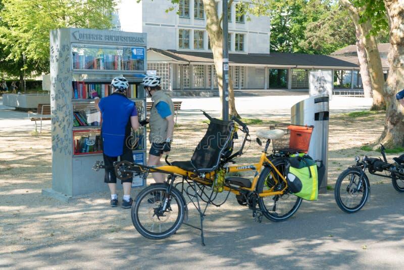 Solothurn SÅ/Schweiz - 2 Juni 2019: biccleturister att stoppa och tycka om böckerna på ett av de fria öppna arkiven i staden fotografering för bildbyråer
