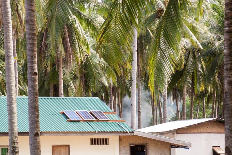 Solpanel på hustaket med solpaneler överst Huset i vändkretsarna bland gömma i handflatan royaltyfria bilder