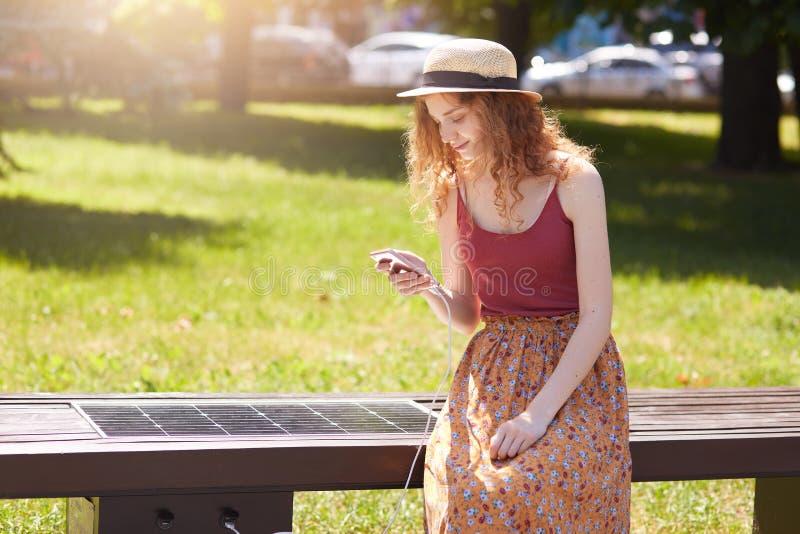 Solpanelen för uppladdning som byggs in i bänk parkerar in rävaktig haired kvinna i tillfällig kläder genom att använda alternati royaltyfri fotografi