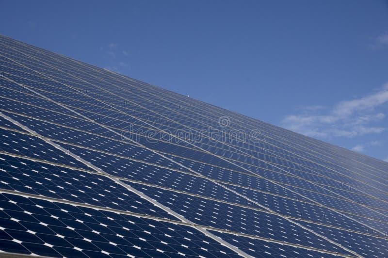 Solpaneler för energi - besparing med blå himmel bakom royaltyfri foto