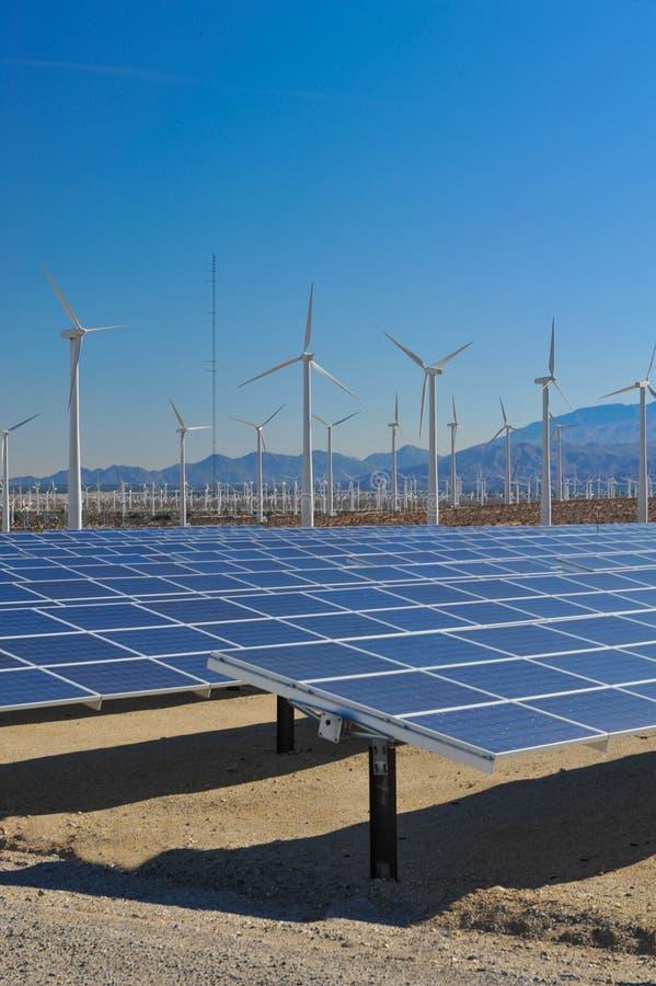 Solpaneler framme av vindturbiner och mountians arkivbild