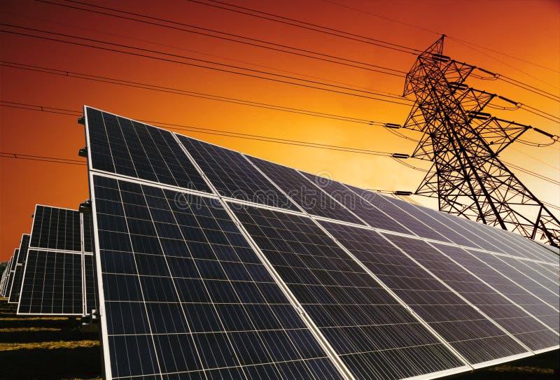Solpaneler med kraftledningbakgrund arkivfoto
