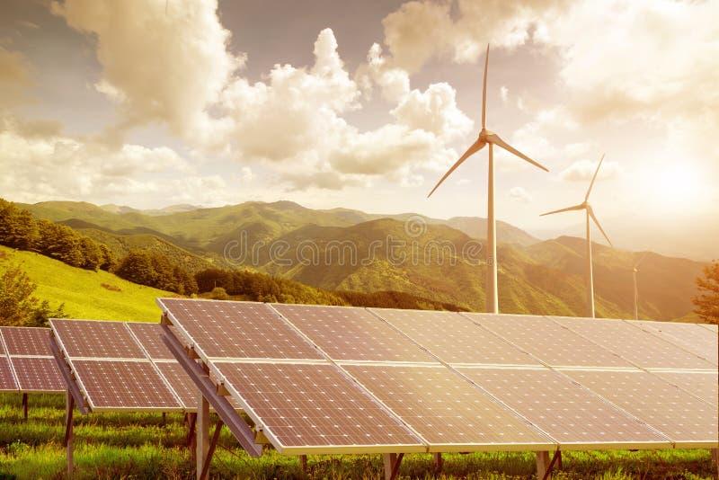 Solpaneler och vindturbiner mot mountanis landskap igen royaltyfria foton