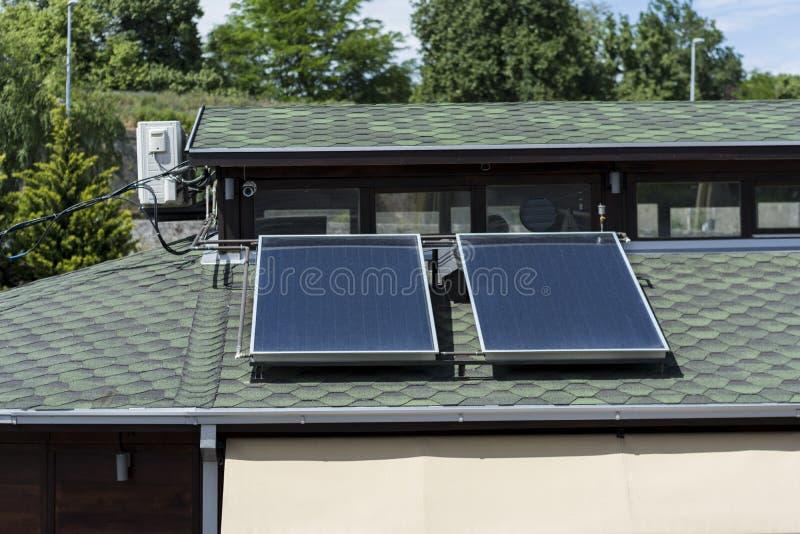 Solpaneler på det gröna taket på hus i natur royaltyfri foto