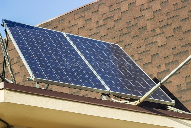 Solpaneler på ett tak av ett hus mot blå himmel fotografering för bildbyråer