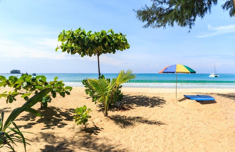 Solparaply och sunbed på den Nai Yang stranden arkivfoto