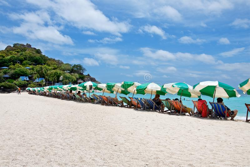 Solparaplyer och solstolar på en vit strand av den Nang Yuan ön royaltyfria foton