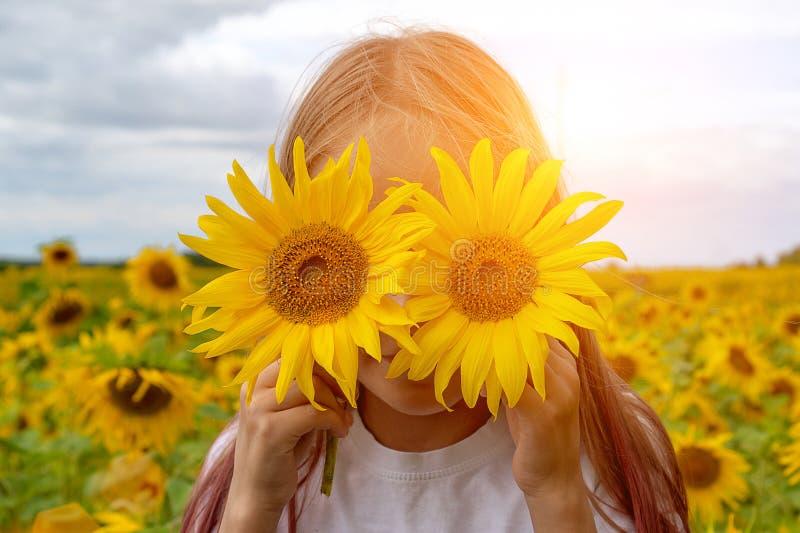 Solrosögon Förtjusande liten flicka som rymmer solrosor i ögon som kikare i trädgården arkivfoton