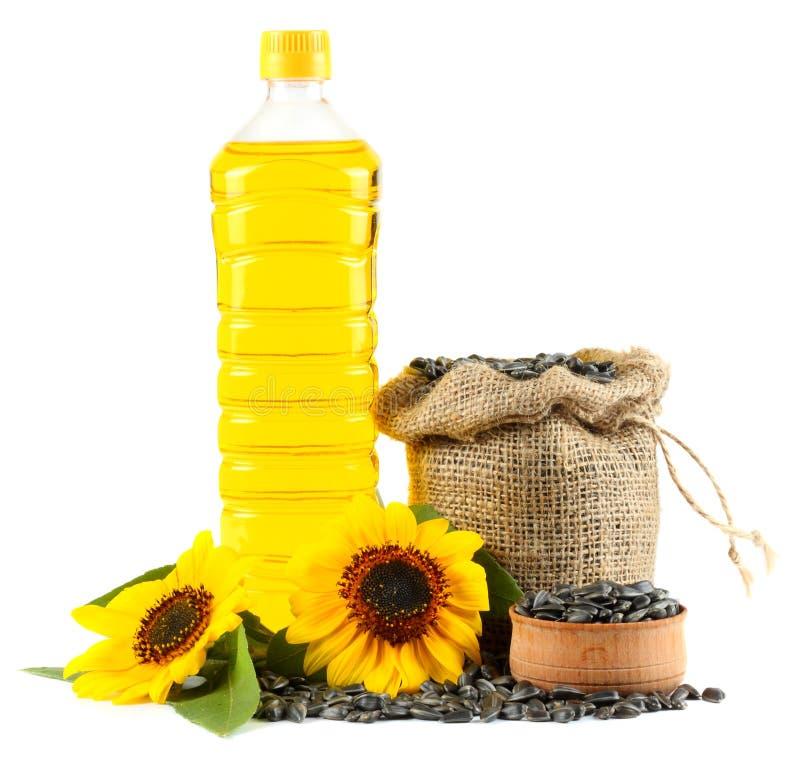 Solrosolja i den plast- flaskan, frö och blomman som isoleras på vit bakgrund royaltyfri fotografi