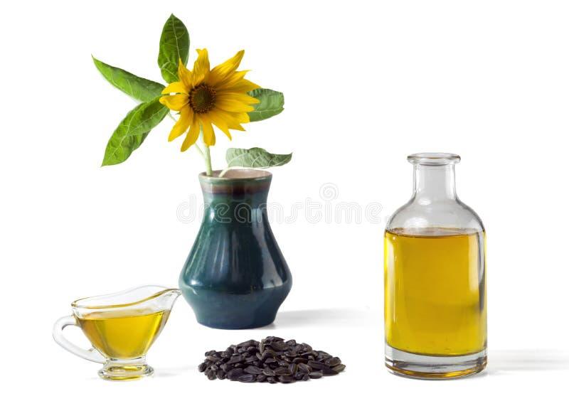 Solrosolja i ett exponeringsglasskyfartyg och i en flaska, grupp av solrosfrö och en solros i en vas royaltyfri foto