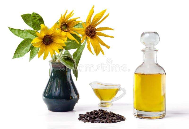 Solrosolja i ett exponeringsglasskyfartyg och i en flaska, handfullsolrosfrö och en solros i en vas royaltyfri fotografi