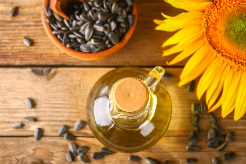 Solrosolja och solrosfrö i liten säck på traditionell lantlig träbakgrund Organisk och ecomatbegrepp Sund foo royaltyfria foton