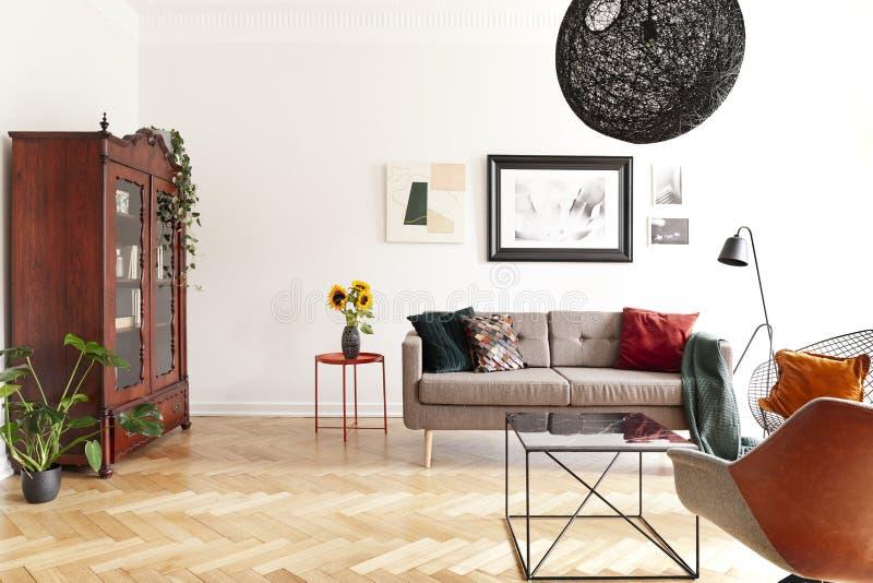 Solrosor på tabellen bredvid soffan i ljus vardagsruminre med affischer och växter Verkligt foto royaltyfri illustrationer