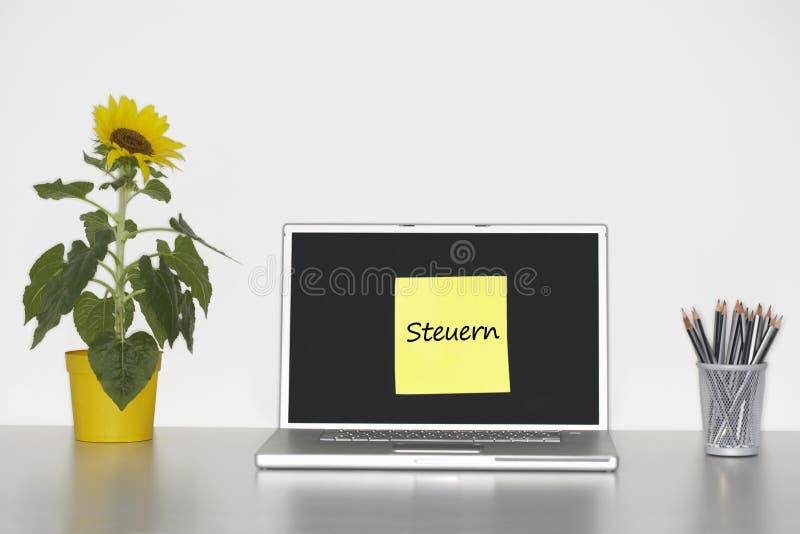 Solrosväxt på skrivbordet och klibbig brevpapper med tysk text på bärbar datorskärmen som säger Steuern (skatter) arkivfoto