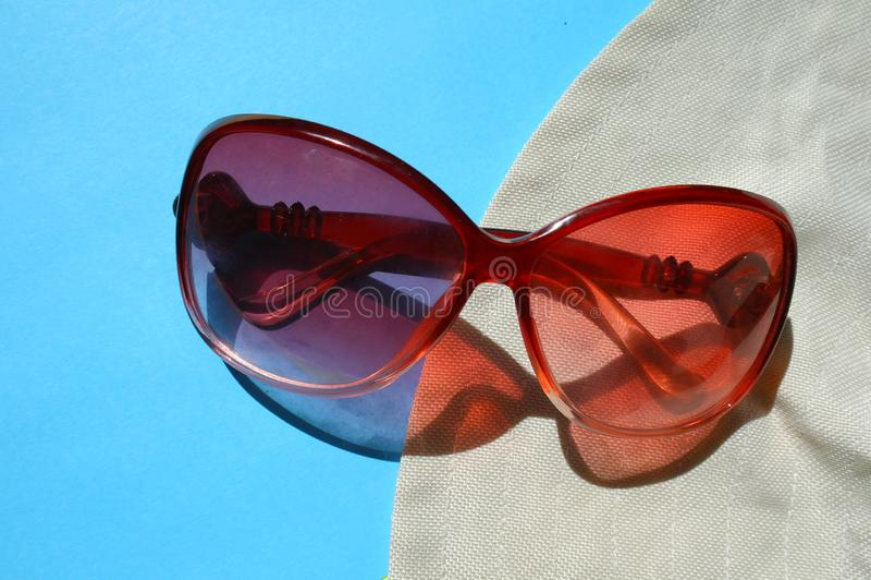 Solsäkerhetsexponeringsglas, hatt på blå bakgrund royaltyfri foto