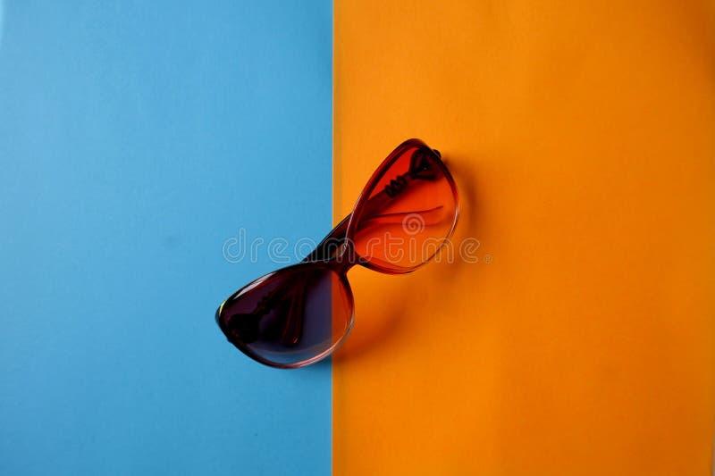 Solsäkerhetsexponeringsglas på blå och orange bakgrund arkivfoton