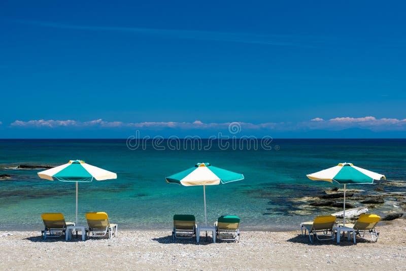 Sols?ngar och ett paraply p? stranden, p? kusten arkivbilder