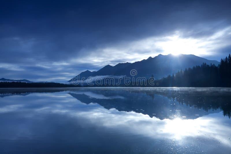 Solsken över berg och den alpina sjön royaltyfria foton