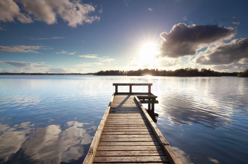 Solsken över träpir på den stora sjön royaltyfria foton