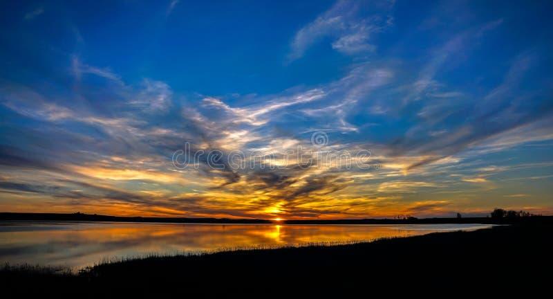 Solsken med färgade moln över sjön och reflektion över vatten royaltyfri bild
