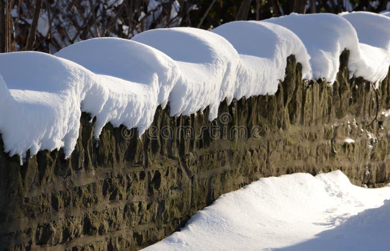 Solsken och locket av ny snö definierar en stenvägg arkivfoton
