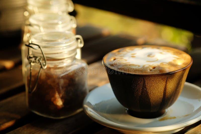Solskumdesignen i varmt lattekaffe och suger på den grova trätabellen royaltyfri foto