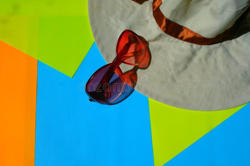Solskyddsglasögon, hatt på blå och gul bakgrund royaltyfri bild
