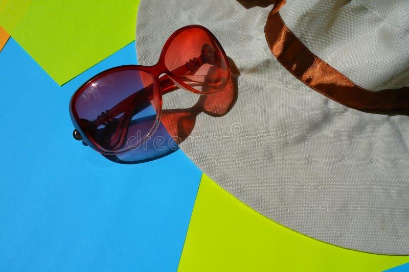 Solskyddsglasögon, hatt på blå och gul bakgrund fotografering för bildbyråer