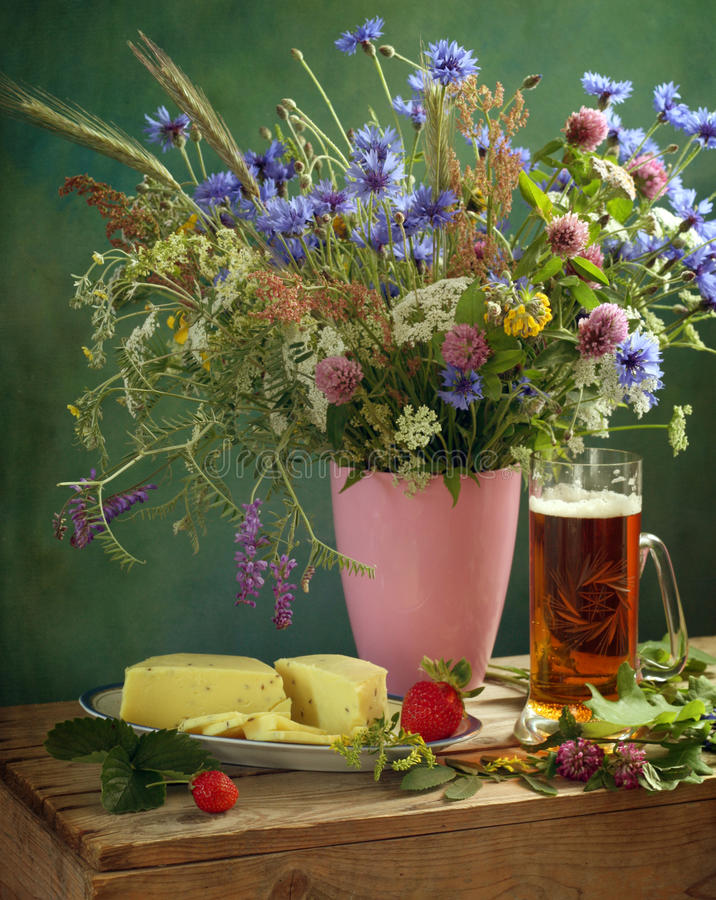 Solstice. Summer solstice still life with flowers and snacks stock images