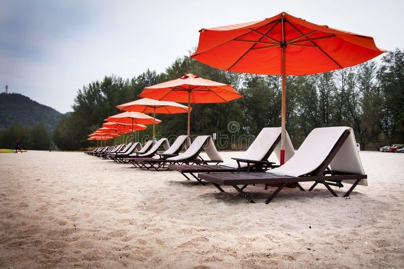 Solstolar och strandparaplyer på stranden arkivbilder