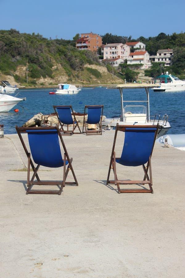 Solstolar på en pir I fjärden av Supetarska Draga, Rab ö, Kroatien arkivfoto