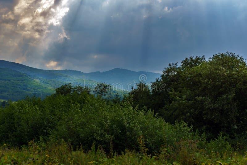 Solstrålar över gröna berg royaltyfria foton