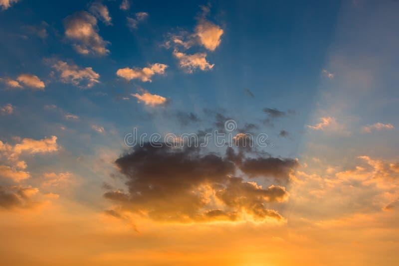 Solstrålar och färgrika moln i blå himmel på solnedgången för bakgrund royaltyfri foto