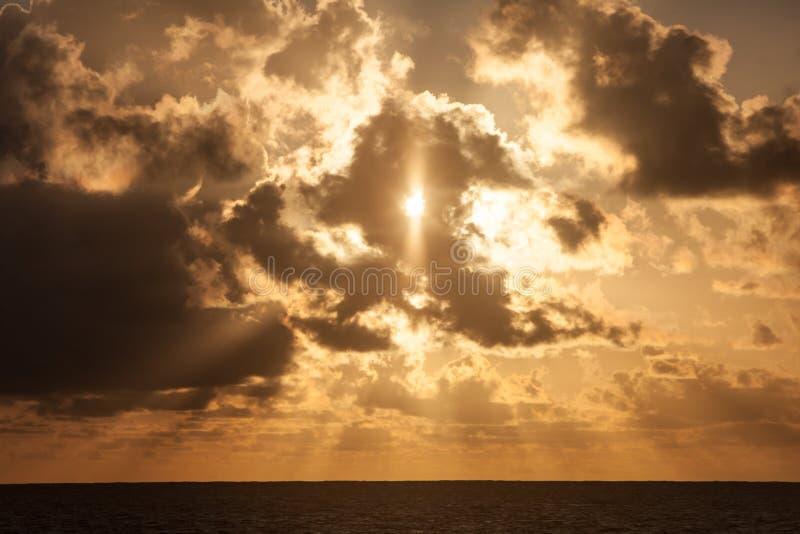 Solstrålar och moln på soluppgång i tropikerna fotografering för bildbyråer