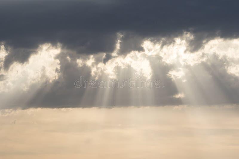 Solstrålar på solnedgången, molnig himmel arkivfoton