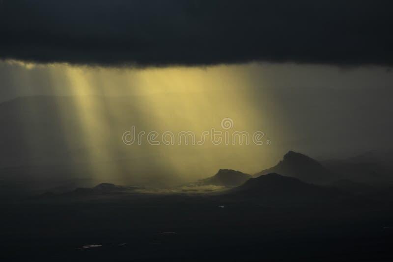 Solstrålar till och med molnen över bergen arkivfoton
