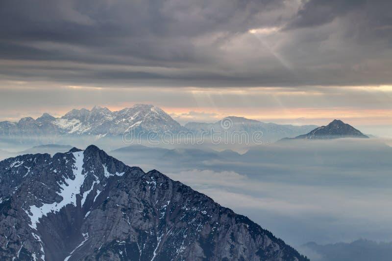 Solstrålbristning till och med mörka moln i Karavanke och Kamnik fjällängar royaltyfri fotografi