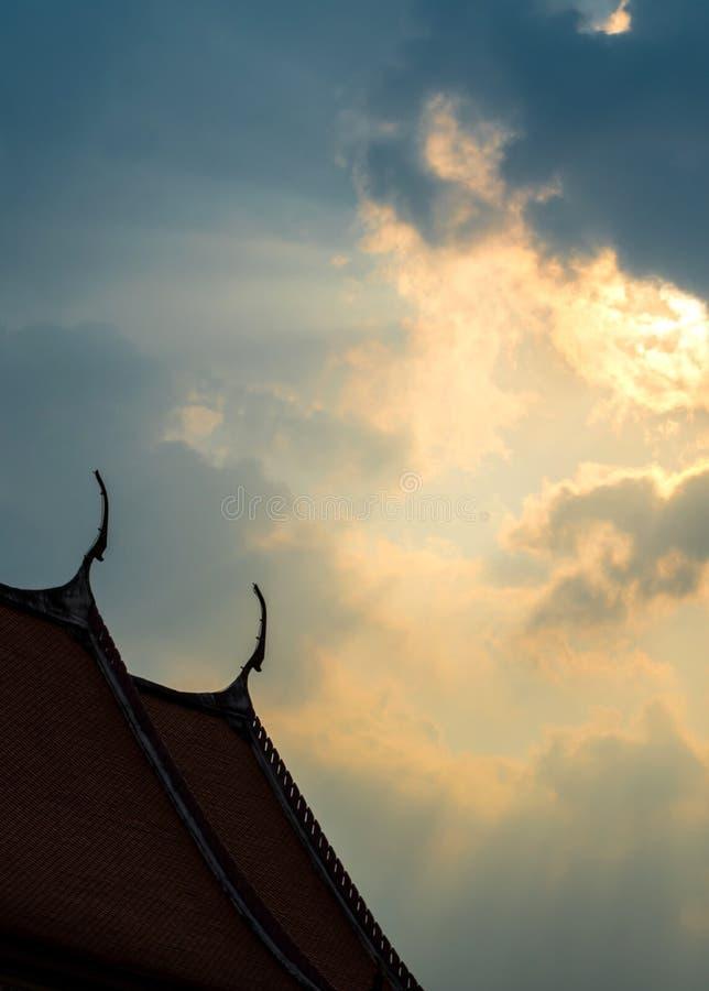 Solstråle bak solnedgångmoln över den buddistiska templet arkivbilder