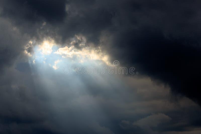 Solstråle i mörkermoln och himmel arkivfoton