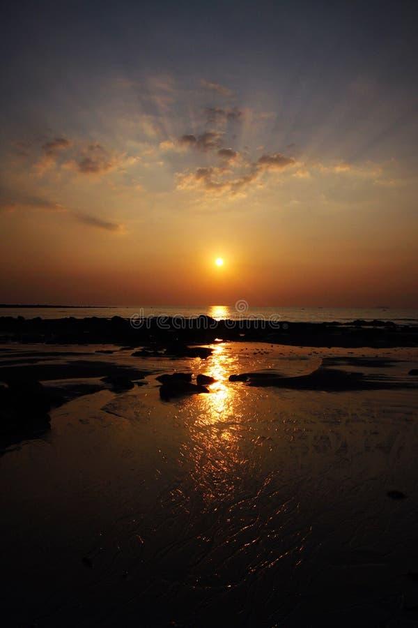 Solstråle under solnedgången som gjuter den långa gula strålen av ljus över havet royaltyfri bild