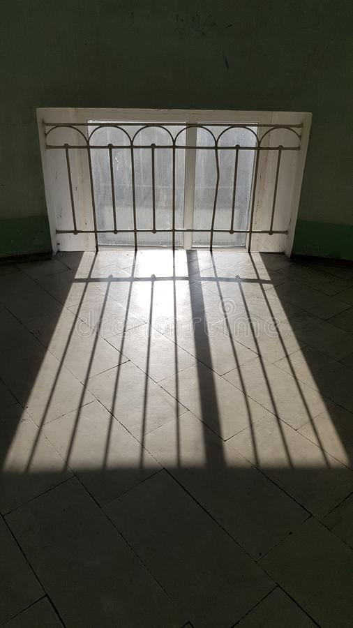 Solstråleband på belagt med tegel golv för sten nära det retro stilfönstergallret arkivbild
