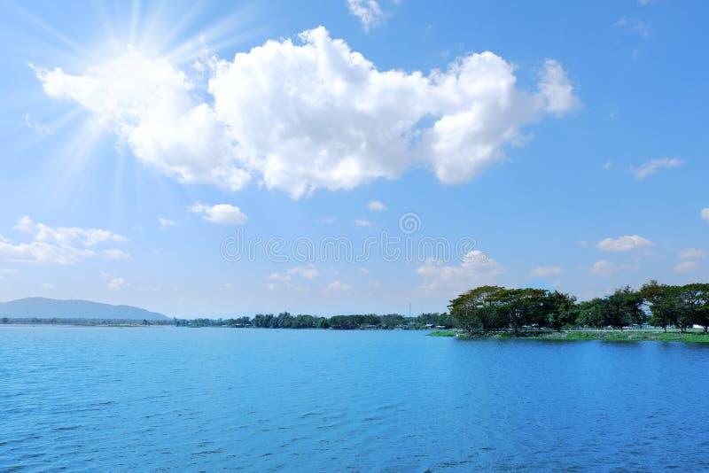 Solstrålljus på blå himmel över stor sjöbakgrund royaltyfri bild