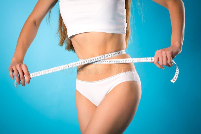 Soltando el peso - la mujer joven está midiendo su cintura imagenes de archivo