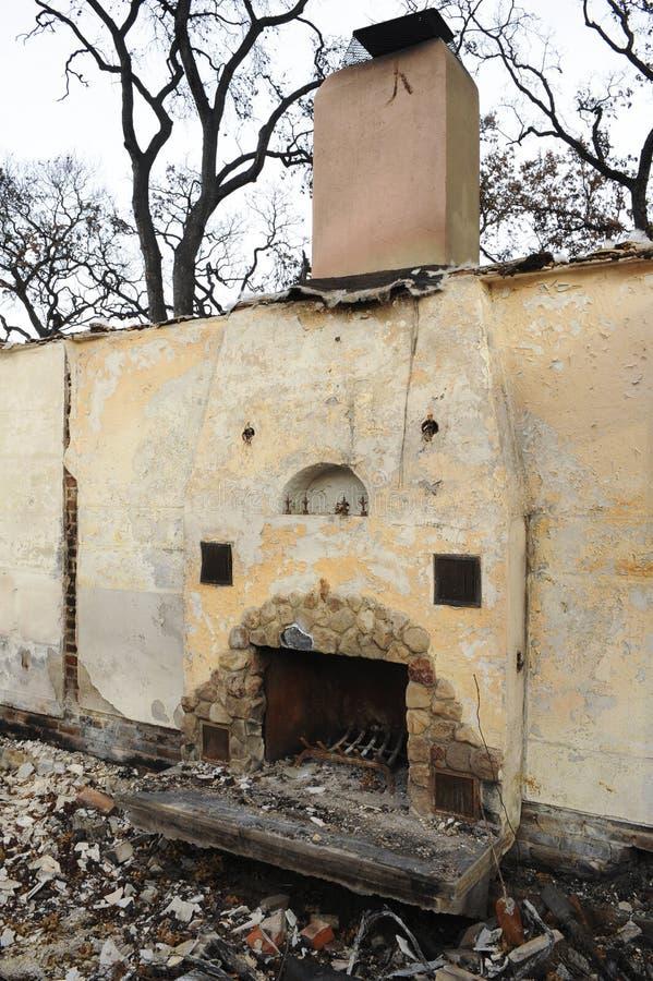 Soltanto un camino sta in mezzo della distruzione carbonizzata di un fuoco della casa fotografia stock