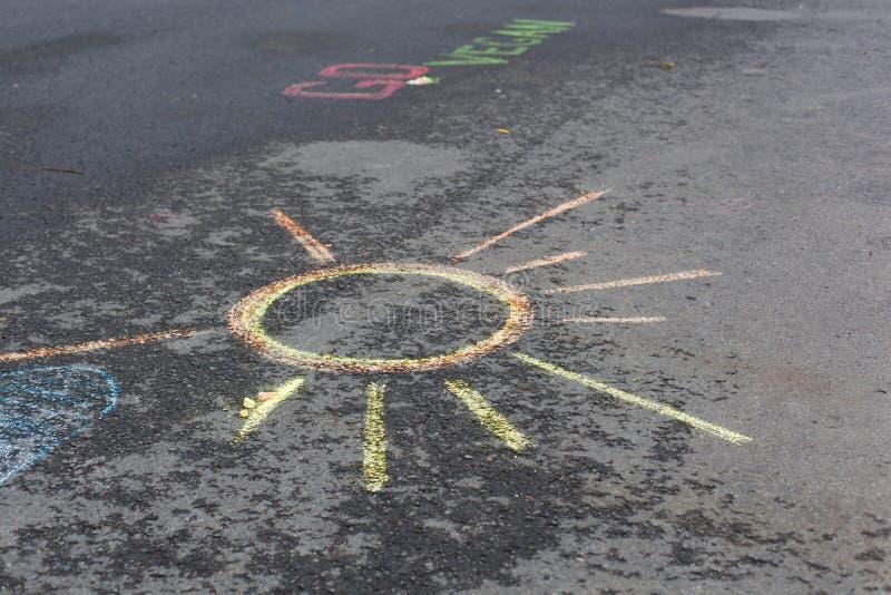 Solteckning på asfalt arkivfoto