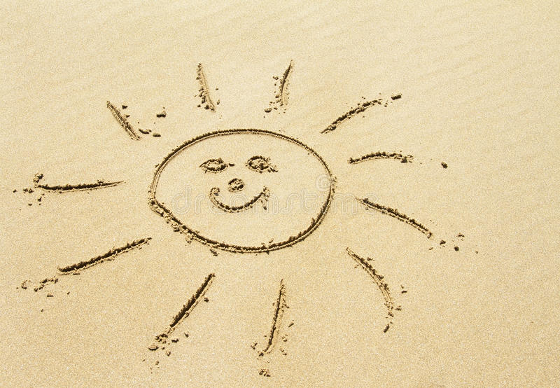 Solteckning på den sandiga stranden arkivbild