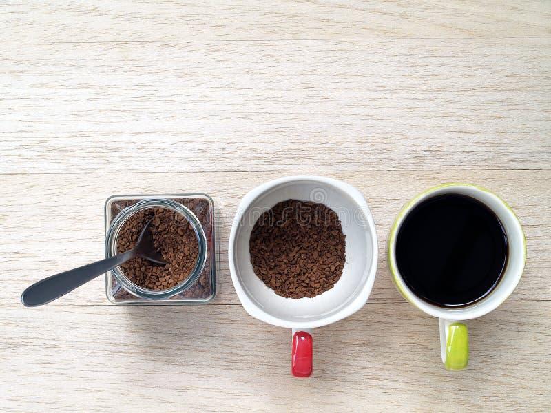Soluble natychmiastowa kawa z srebną herbacianą łyżką w szklanym słoju z kawa proszkiem w filiżance i warząca czarna kawa w innej obraz stock