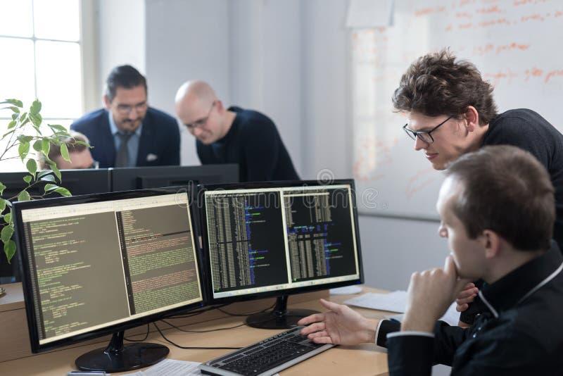 Soluci?n de problemas de lanzamiento de negocio Desarrolladores de software que trabajan en el equipo de escritorio imágenes de archivo libres de regalías