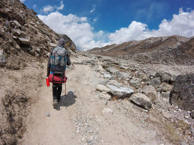 Solukhumbu Valley, Nepal - May 2019: young backpacker man trekking to the Everest Base Camp in a sunny day royalty free stock images