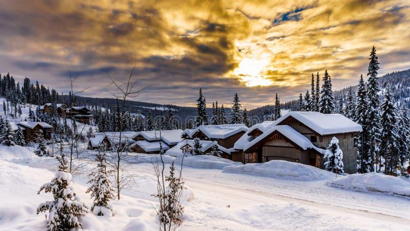 Soluppgång över dold by för snö arkivbilder